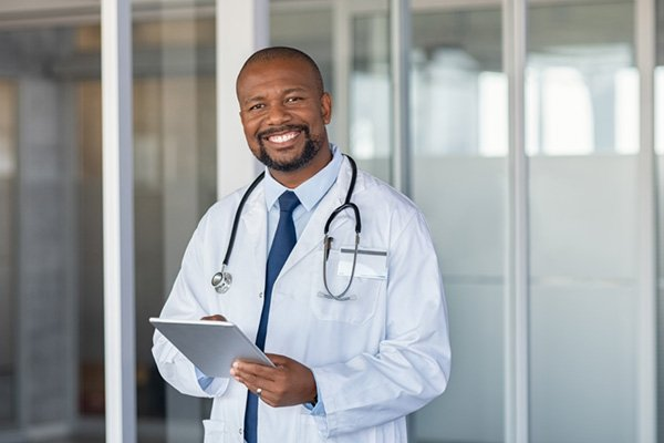 male doctor smiling with clipboard